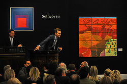 © Licensed to London News Pictures. 05/10/2017. London, UK.  (L to R) 'Homage To The Square: Temperate', 1957, by Josef Albers sold for hammer price of GBP1,900k (Est. GBP700-1,000k) and '15 Canvas Study Of The Grand Canyon', 1998, by David Hockney sold for a hammer price of GBP5,200k (Est. GBP3,800-5,000k) at the Italian and Contemporary Art evening auction at Sotheby's, New Bond Street, coinciding with the opening of the London's Frieze Art Fair. Photo credit : Stephen Chung/LNP