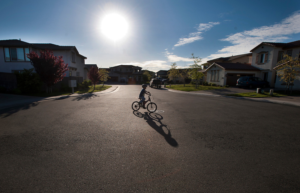 Justin Hinson rides around in circles waiting for the rest of the family to join him for a bike ride. March 11, 2011.