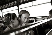 IPLM0134 , South Africa, Excelsior. October 2003. Two little Afrikaans girls on the school bus on their way home after a day at the CVO school, a school focused on delivering schooling based on Afrikaner culture and Christian values. AFR001; Afrikaner; youth; rural; transport; Bus; Girls; School; Afrikaans. Leonie Marinovich