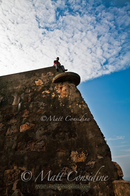 Sitting on the ramparts of an old Portuguese fort looking out to sea.<br /> (Photo by Matt Considine - Images of Asia Collection)