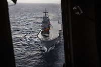 "INTERNATIONAL WATERS (OFF THE COASTS OF SICILY, ITALY) - 9 FEBRUARY 2017: The San Giorgio, an amphibious transport dock of the Italian Navy, is seen here from a helicopter of the Italian Navy in international waters off the coast of Sicily, Italy, on Febuary 9th 2017.<br /> <br /> As a consequence of the April 2015 Libya migrant shipwrecks, the EU launched a military operation known as European Union Naval Force Mediterranean (EUNAVFOR Med), also known as Operation Sophia, with the aim of neutralising established refugee smuggling routes in the Mediterranean. The aim of this new operation launched by Europe is to undertake systematic efforts to identify, capture and dispose of vessels as well as enabling assets used or suspected of being used by migrant smugglers or traffickers. On 20 June 2016, the Council of the European Union extended Operation Sophia's mandate reinforcing it by supporting the training of the Libyan coastguard.<br /> Thus far, following EUNAVFOR MED operation Sophia's activities, 101 suspected smugglers and traffickers have been apprehended and transferred to the Italian<br /> authorities and 380 boats were removed from the criminal organizations' availability. The Operation has saved 32.081 migrants, among whom 1888 children.<br /> <br /> On February 2nd 2017 Italian Premier Paolo Gentiloni and Prime Minister of the U.N. backed Libyan government Fayez al-Serraj signed a memorandum of understanding on cooperation to combat illegal migration, human trafficking and contraband and on reinforcing the border between Libya and Italy. The following day, as EU leaders meet in Malta for a summit, European Council President Donald Tusk said after talks with Serraj, that ""it is time to close the (migrant) route from Libya to Italy"" and that ""the EU has shown it is able to close the routes of irregular migration, as it has done in the eastern Mediterranean.""  Tusk said the Central Mediterranean route was ""not sustainable either for the EU or for Libya"", where he said trafficker"