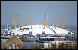 The London O2 arena, owned by Anschutz Entertainment Group, is seen against a backdrop of the Canary Wharf business and financial district in London, UK. on April 23, 2013. The Office for National Statistics said its preliminary estimates for gross domestic product (GDP), showed the economy grew by 0.3% in the first three months of the year. The figure means the economy avoided two consecutive quarters of contraction - the definition of a recession, April 25, 2013. Photo by: Andrew Parsons / i-Images