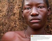 Benin, Natitingou November 30, 2006 - Man with tribal scarification on his face. Scarification is used as a form of initiation into adulthood, beauty and a sign of a village, tribe, and clan. ©Jean-Michel Clajot
