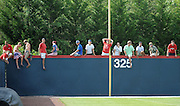 Milton fans sit atop the left field wall in their GHSA AAAAAA State Baseball Championship game against Roswell, Monday, May 27, 2013, in Milton, Ga.   David Tulis/AJC Special