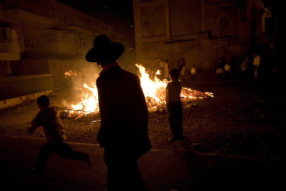 An orthodox Jew walks past celebrations of Lag Ba'omer in a district of Jerusalem. 22nd May 2008