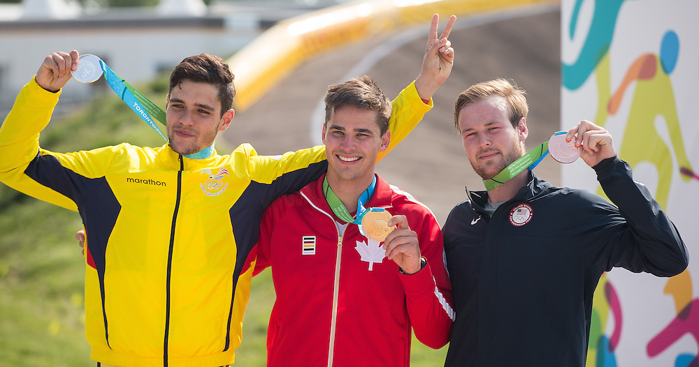 Gold medalist Tory Nyhaug (C) of Canada celebrates his win in the BMX  with silver medalist Alfredo Campo Vintimilla of Ecuador (L) and bronze medalist Nicholas Long during the BMX medal ceremony at the 2015 Pan American Games in Toronto, Canada July 11,  2015.  AFP PHOTO/GEOFF ROBINS
