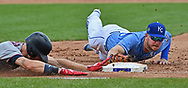 Kansas City Royals first baseman Ryan O'Hearn (R) makes a diving tag with his glove at first base, to force out Minnesota Twins center fielder Max Kepler (L), diving head first into first base, during the fourth inning at Kauffman Stadium.