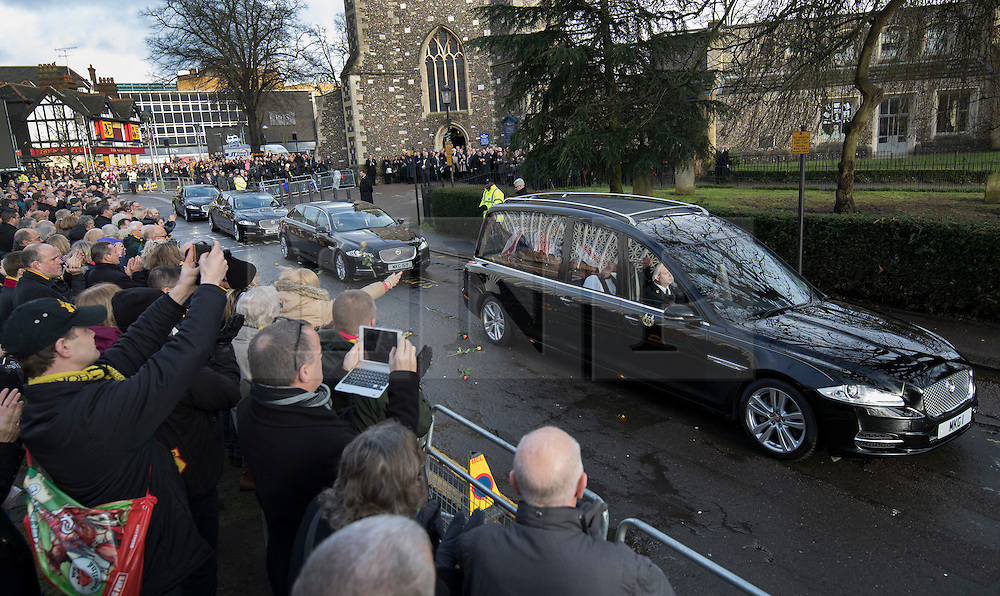 © Licensed to London News Pictures. 01/02/2017. Watford, UK. Mourners (L) throw flowers as the coffin of England football team manager Graham Taylor leaves St Mary's Church in Watford, Hertfordshire after his funeral. The former England, Watford and Aston Villa manager,  who later went on to be chairman of Watford Football Club, died at the age of 72 from a suspected heart attack. Photo credit: Peter Macdiarmid/LNP
