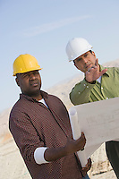 Construction workers studying blueprints outdoors