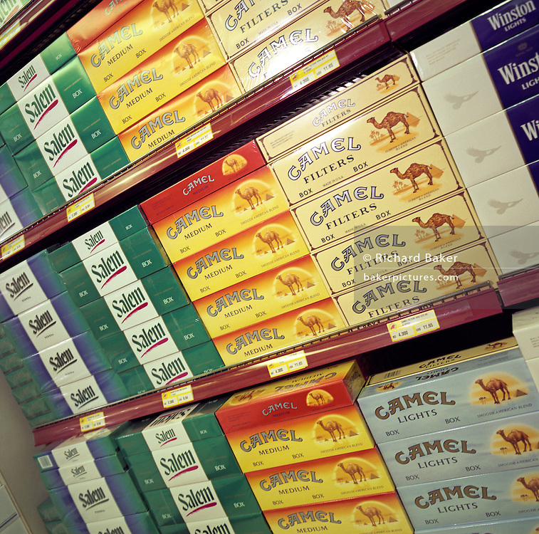 Stacks of cigarette cartons are piled up in a display of duty free goods at Bahrain International airport . Camel Filters are featured more prominently here to suggest the importance of desert Gulf States like Bahrain in the global market. Bahrain is a key hub airport in the region, providing a gateway to the Northern Gulf. The airport is the major hub for Gulf Air which provides 52% of overall movements. It is also the half-way point between Western Europe and Asian destinations such as Hong Kong and Beijing. Duty free merchandise such as tobacco, jewellery, perfumes and electronics are big business here, favouring cheaper import duties and currency rates. Picture from the 'Plane Pictures' project, a celebration of aviation aesthetics and flying culture, 100 years after the Wright brothers first 12 seconds/120 feet powered flight at Kitty Hawk,1903.