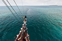 Pinisi liveaboard diving boat navigating the narrow channel into Mapia Atoll 's lagoon, West Papua, Indonesia.