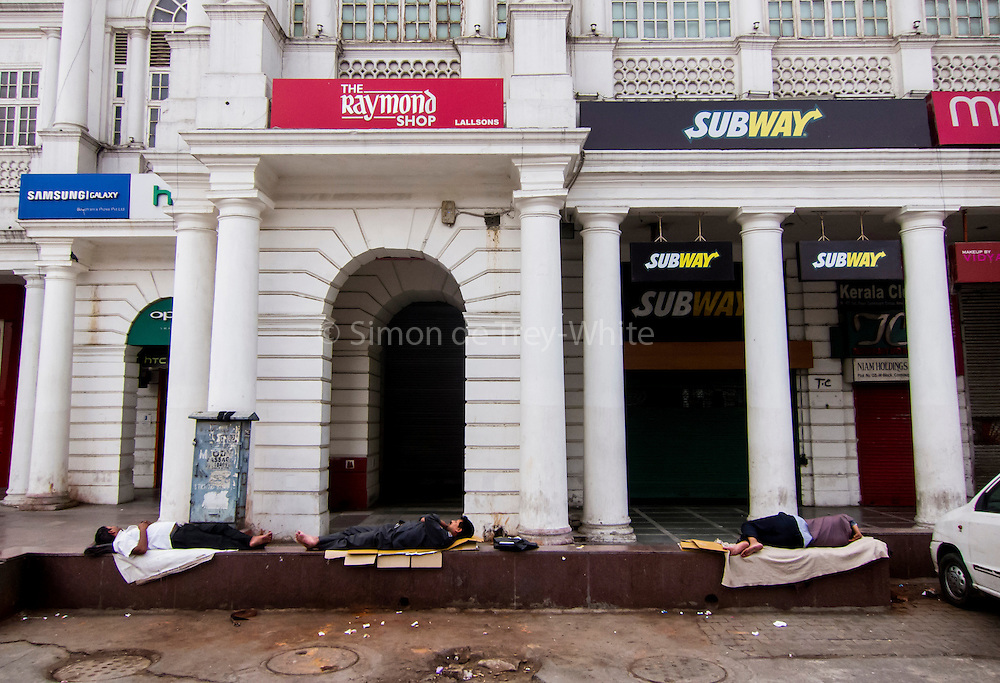 16th April 2016, New Delhi. Men sleep on a wall in Connaught Place in New Delhi, India on the 16th April 2016<br /> <br /> Sleeping in the outdoors is common in Asia due to a warmer climate and the fact that personal privacy for sleep is not so culturally ingrained as it is in the West. New Delhi (where most of these images were taken) is a harsh city both in climate and environment and for those working long hours, often in hard manual labour, sleep and rest is something fallen into when exhaustion overwhelms, no matter the place or circumstance. Then there are the homeless, in Delhi figures for them from Government and NGO sources vary wildly from 25,000 to more than 10 times that. Others public sleepers may simply be travellers having a siesta along the way.<br /> <br /> PHOTOGRAPH BY AND COPYRIGHT OF SIMON DE TREY-WHITE, photographer in Delhi<br /> <br /> + 91 98103 99809<br /> email: simon@simondetreywhite.com