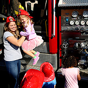 TONED CTY SAFETY10<br /> <br /> Beth Ryan, a Pre-K teacher, left, helps Morgan Stacy, 4, of Sylvania, down from inside the fire truck brought during a fire safety presentation by the Toledo Fire and Rescue Department for the Pre-K class at Love 'n Learn Educational Child Care in Toledo on Tuesday, October 9, 2018. THE BLADE/KURT STEISS