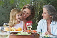 Grandmother mother and daughter (5-6) sitting at table in garden