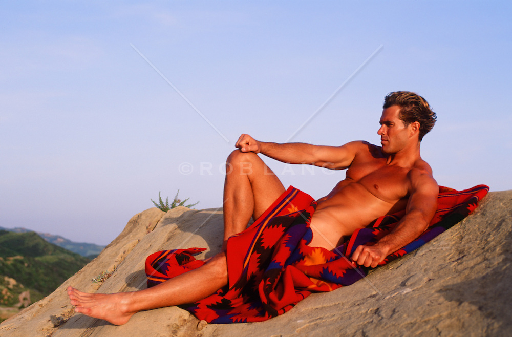 nude man in a blanket on a rock formation