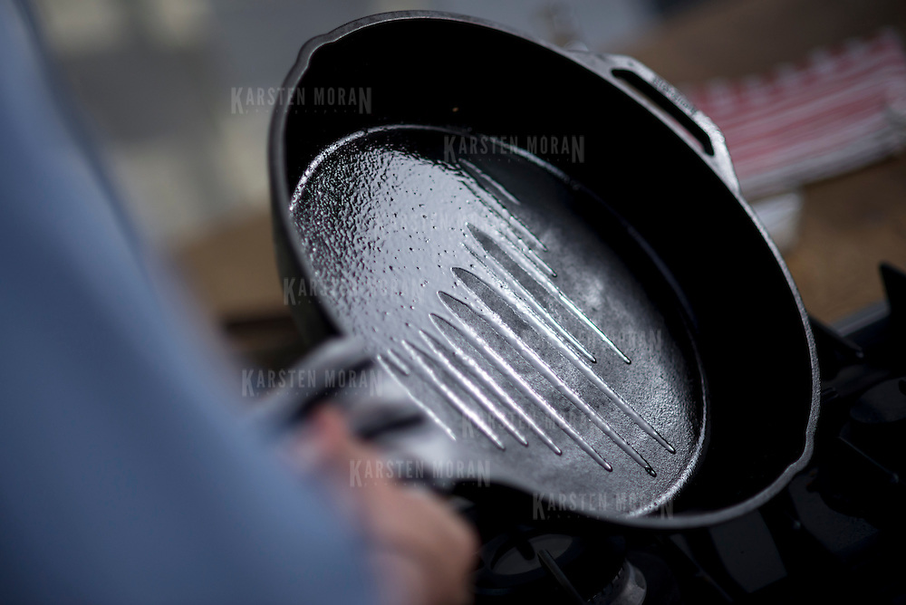 June 11, 2014 - New York, NY : New York Times writer and editor Sam Sifton prepares a cast iron pan to cook hamburgers in, during a studio shoot in Brooklyn on Wednesday morning. Sifton makes the burgers in a skillet so they can cook in their own juices. CREDIT: Karsten Moran for The New York Times