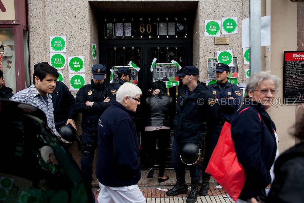 A resident enters through a police line the building where Popular Party Deputy Mari Luz Prieto lives while anti-eviction activists take part in a 'escrache' , on April 4, 2013 in Madrid, Spain. Stickers read 'Yes we can'. The Mortgage Holders Platform (PAH) and other anti evictions organizations are organizing 'escraches' for several weeks under the slogan 'There are lifes at risk' to claim the vote for a Popular Legislative Initiative (ILP) to stop evictions, regulate dation in payment and social rent outside Popular Party deputies' houses and offices..'Escraches' are form of peaceful public protest that was used in Argentine in 1995 to point to pardoned genocides of Argentenia's Dictatorship within their neighborhoods.