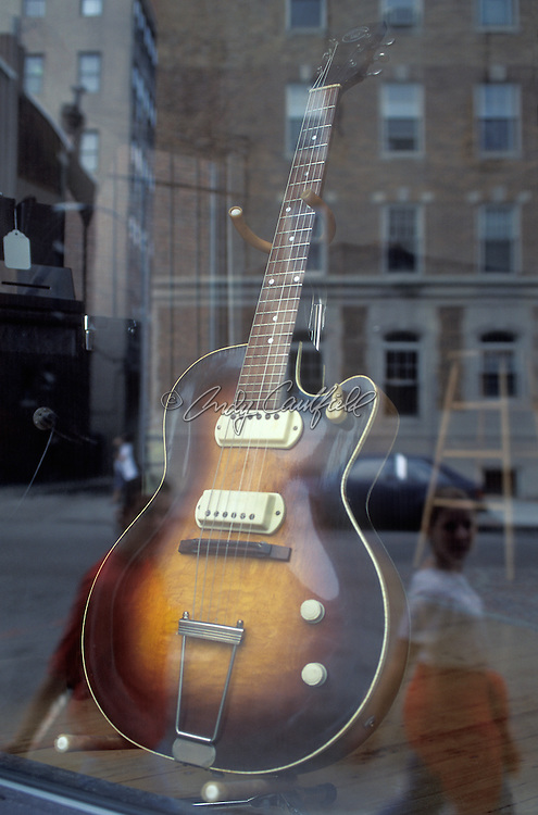 Club window with guitar and reflection on Newbury street, Bpston, MA.