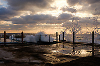 HAVANA, CUBA - CIRCA MARCH 2017:  Ocean waves crashing an abandoned field in Havana at sunset.