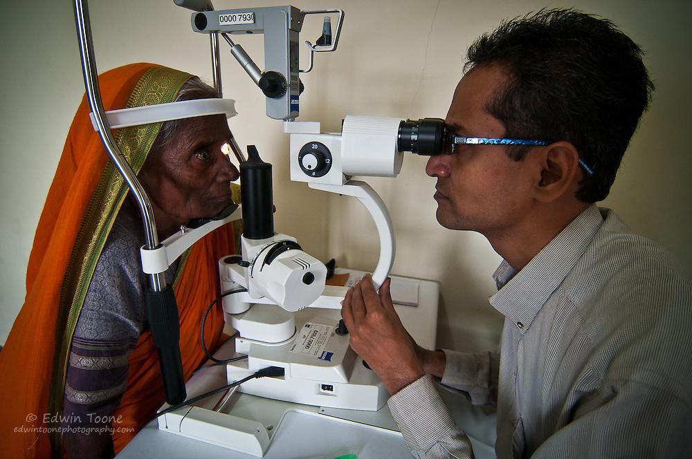 A visiting eye doctor does an eye exam.