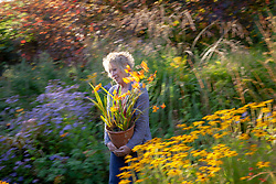 Carol Klein carrying pot of crocosmia at Glebe Cottage