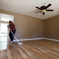 Thomas Wells | Northeast Mississippi Daily Journal<br /> LaTonya Hobson finishes mopping the floor for her friend, Tamara Norman, before Monday's dedication of Norman's new Habitat for Humanity home.