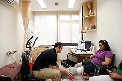 Prosthetist Trevor Binedell (L) makes a cast for Aishah's prosthetic legs at Tan Tock Seng Hospital in Singapore 25 June 2014. She has to make a new set of prothetic legs as her old ones are too big for her and hurts her when she walks.