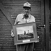 "The late John ""Jack"" Murnaghan, a retired union organizer holding a retirement gift which is a photo of the Macassa Mine where he worked for 43 years.  At the time this photograph was taken, Murnaghan was living alone and suffering from Alzheimer?s disease, Kirkland Lake, Ontario.  From the book Cage Call: Life and Death in the Hard Rock Mining Belt. An in-depth project spanning over 12-years examining communities in one of the richest mining regions in the world located in Northwestern Ontario and Northeastern Quebec in Canada."