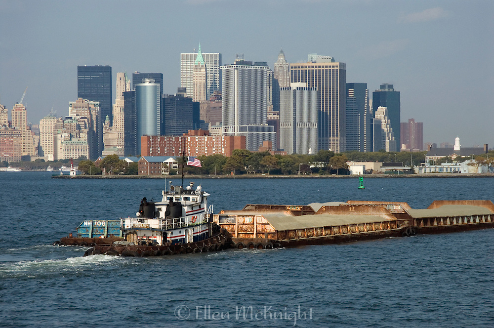 Tugboat pushing a Barge in front of Governor's Island and Lower Manhattan