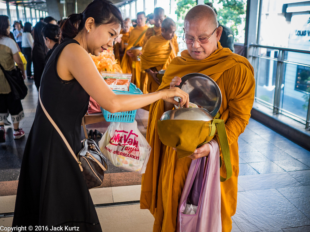 "29 NOVEMBER 2016 - BANGKOK, THAILAND:  Buddhist monks collect alms from people during a special ""tak bat"" or merit making ceremony in the Ratchaprasong skywalk of the Bangkok BTS system. The tak bat was to honor Bhumibol Adulyadej, the Late King of Thailand. Food and other goods were given to the monks, who in turn gave the items to charities that will distribute them to Bangkok's poor. More than 100 Buddhist monks participated in the merit making ceremony. The ceremony was organized by the merchants in the Ratchaprasong Intersection, which includes some of Bangkok's most upscale shopping centers.     PHOTO BY JACK KURTZ"