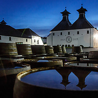 Ardbeg Distillery is reflected in water pooled on top of barrels in Port Ellen, Isle of Islay, Scotland, July 15, 2015. Gary He/DRAMBOX MEDIA LIBRARY