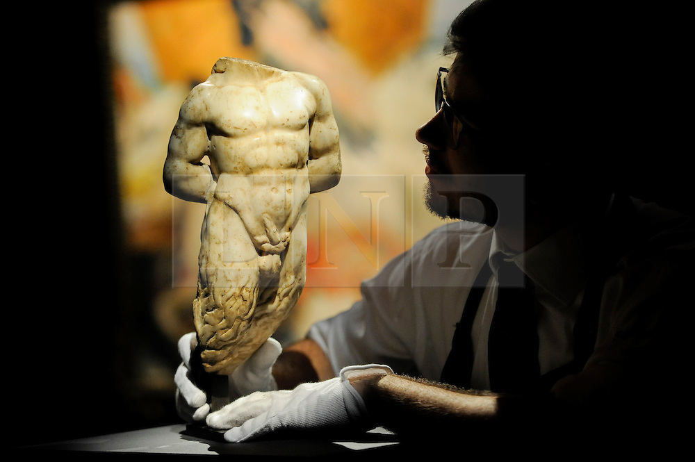 """© Licensed to London News Pictures. 10/02/2017. London, UK.  A technician inspects a 2nd century Roman Marble Torso of Pan (est. GBP40-60k), at the preview of the """"Erotic: Passion & Desire"""" sale at Sotheby's in New Bond Street.  The sale, which will take place on 16 February, encompasses representations of love and sex from antiquity to the present day.  Photo credit : Stephen Chung/LNP"""