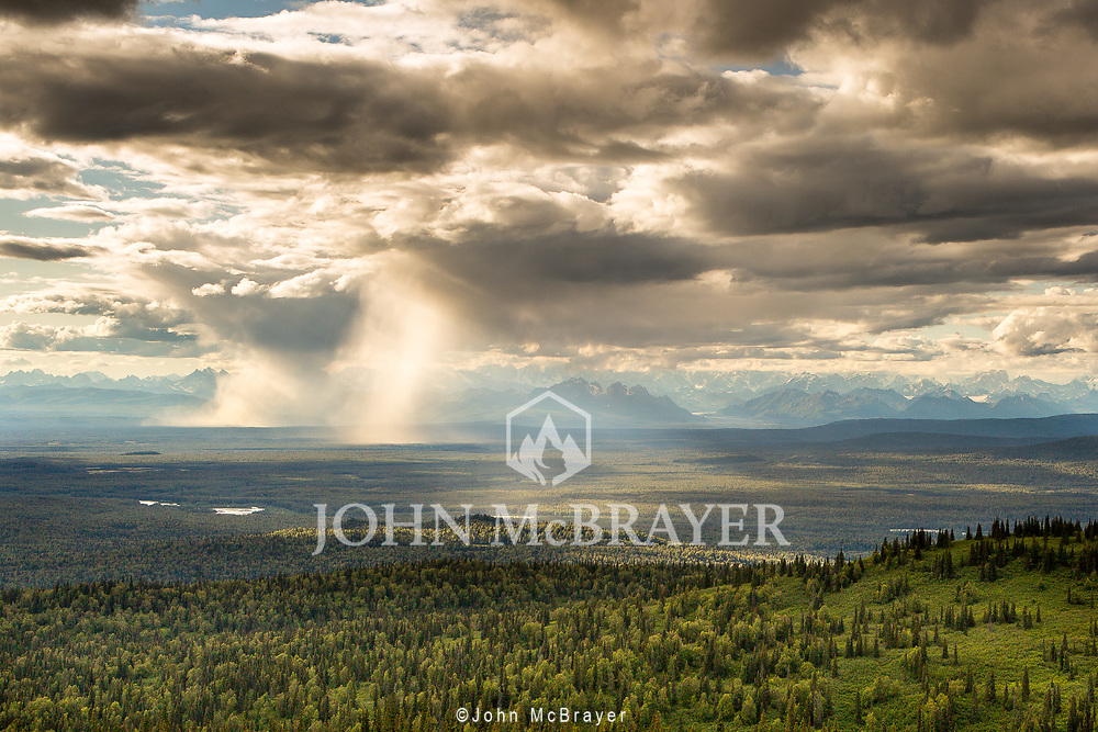 Rain falls in the Susitna River Valley partially obscuring the Denali Range in the background. © John McBrayer
