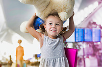 Portrait of cute little girl carrying her big teddy bear in airport with yellow lens flare