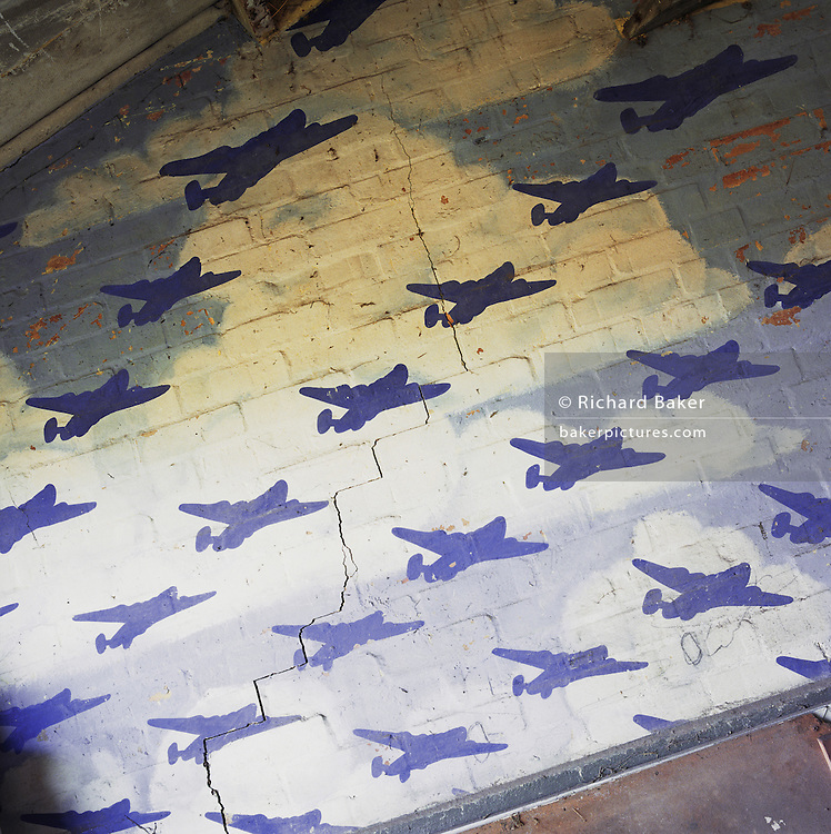 In a farmer's tool shed, a painted mural depicting B-24 Liberators sweeping over the cracked brick wall of what was once an officers? mess at the WW2 Wendling airfield, Norfolk England. Below this scene of heroic military might, young officers flying Liberators of the 392nd Bomb Group gathered before and after raids into Germany from November 1943 to July 1945. The runway is now partly covered by a turkey farm and this building is now full of car and tractor parts. Picture from the 'Plane Pictures' project, a celebration of aviation aesthetics and flying culture, 100 years after the Wright brothers first 12 seconds/120 feet powered flight at Kitty Hawk,1903. .