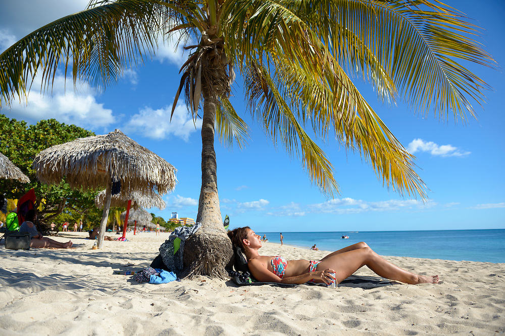 A woman from Europe lays in the sun at the base of a palm tree at Playa Ancon, which is located several kilometers outside the colonial town of Trinidad, Cuba.