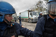 ITALY, GIUGLIANO : Riot police secure the passage of garbage lorries to the Taverna del Re dump in Giugliano on November 2, 2010. Demonstrators protest against the re-opening of the Taverna del Re dump taht contains more than six milion tons of garbage.  AFP PHOTO / ROBERTO SALOMONE