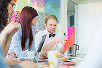 Businessman explaining documents to female colleagues in creative office