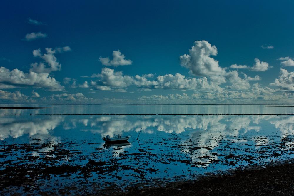 Small boat and morning cloud reflections on Kaneohe Bay, Hawaii