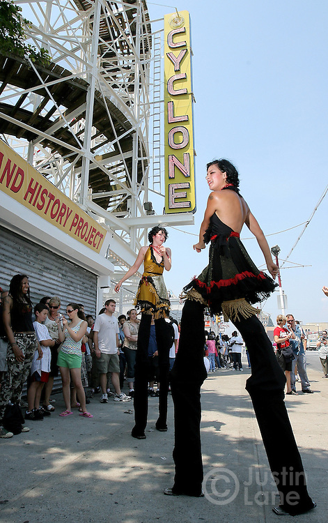 Two women on stilts Anya Sapozhnikova (R) and Kae Burke (L) entertain people waiting in line to ride the Cyclone roller coaster during a 80th anniversary celebration of the famous ride's first run in the Coney Island area of Brooklyn, New York on 26 June 2007.