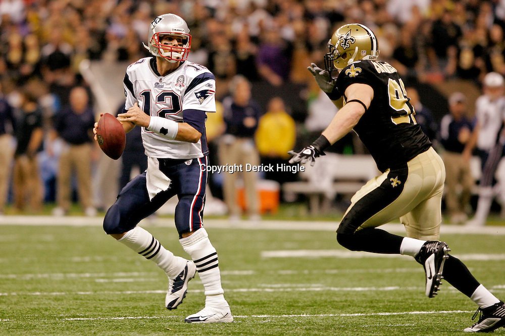 2009 November 30: New England Patriots quarterback Tom Brady (12) runs from New Orleans Saints defensive end Jeff Charleston (97) during a 38-17 win by the New Orleans Saints over the New England Patriots at the Louisiana Superdome in New Orleans, Louisiana.