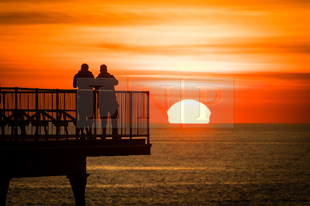 © Licenced to London News Pictures<br /> <br /> 24 June 2018 . Aberystwyth Wales UK<br /> <br /> UK Weather:  People silhouetted standing at the end of the pier in Aberystwyth as the sun sets dramatically over Cardigan Bay  at the end of yet another scorchingly hot  and sunny day.<br /> <br /> The UK is heading  into a mini heatwave, with temperatures forecast to hit 29º or 30º Celsius by the middle of the week<br /> <br /> photo creditKeith Morris/LNP