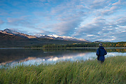Man watching morning alpenglow on Primrose Ridge above Otto Lake, Healy, Alaska