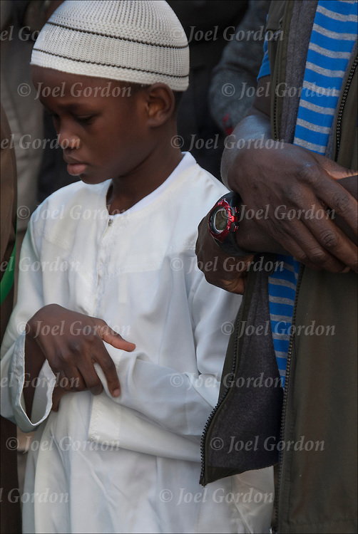 Gambia Afro Muslim father and son ( 1st generation Afro Muslim American ) 9 year old son wearing traditional white Sunmah clothing and skull cap noon prayer in New York City.<br /> <br /> release # 2661