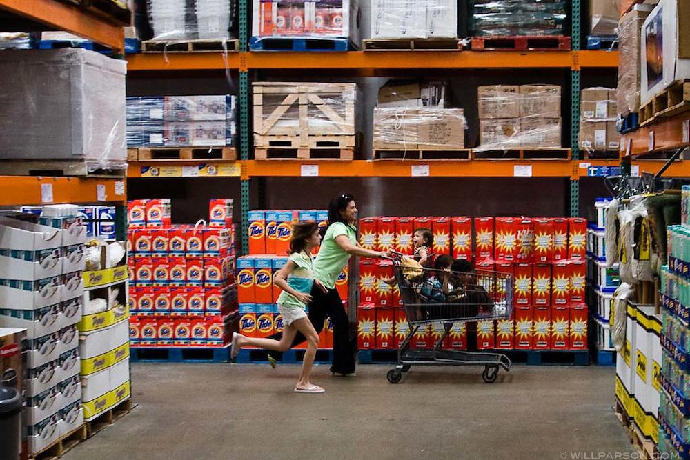 A family runs down an aisle at a Costco warehouse store.