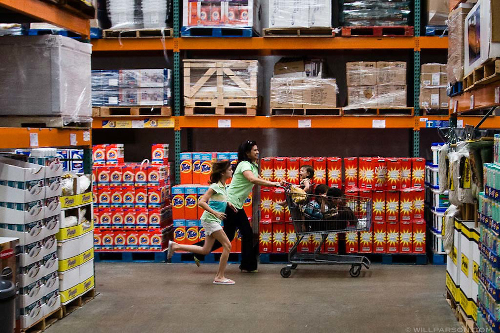 A family runs down an aisle at a Costco warehouse store.