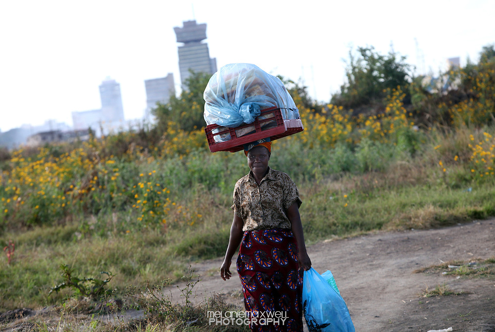 With the Lusaka city skyline in the distance, a woman balances bags of rolls on her head as she makes her way through a compound in Lusaka, Zambia on Thursday, May, 7 2009. The compound is home to around 80,000 people, most of which live in poverty.