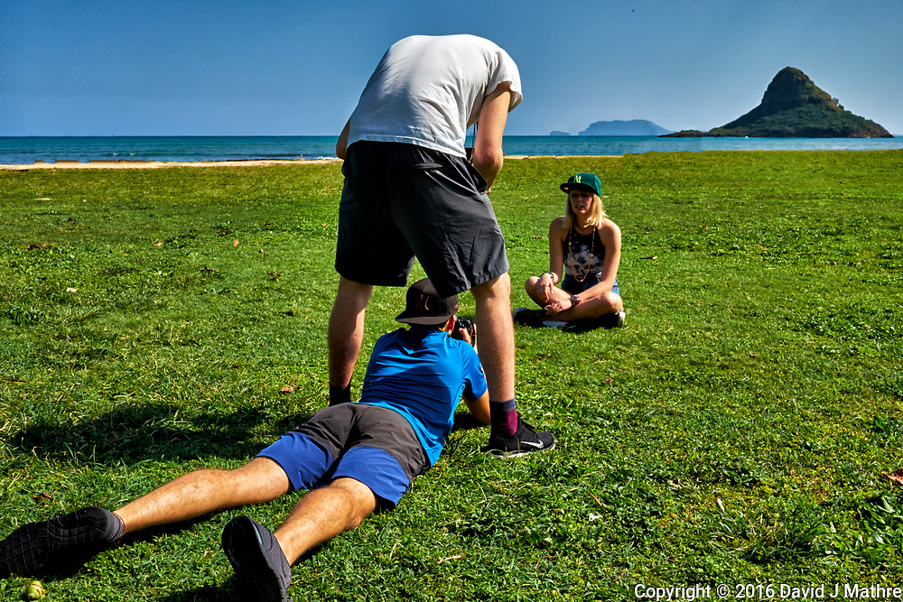 Student being photographed with Mokoli?i (Chinaman's Hat) in the background. Kualoa Regional Park on the north shore of Oahu. Image taken with a Fuji X-T1 camera and 23 mm f/1.4 lens (ISO 200, 23 mm, f/16, 1/250 sec).