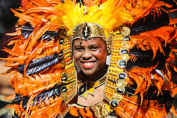 © Licensed to London News Pictures. 29/08/2016. Leeds, UK. A woman dressed in a brightly coloured feathered headdress  dances at the Leeds West Indian Carnival in Leeds, West Yorkshire. First run in the 1960's, the Leeds West Indian Carnival is Europe's longest running authentic Caribbean carnival parade. Photo credit : Ian Hinchliffe/LNP