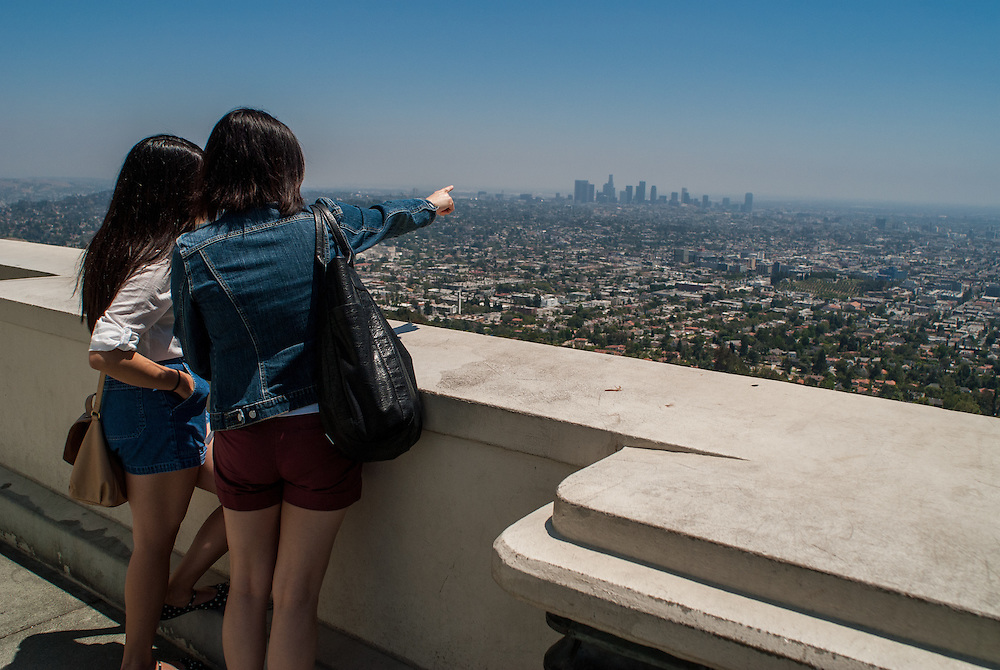 Japanese tourists pointing the Los Angeles downtown out from the top of LA Griffith observatory.